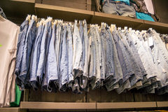 Mans wear - different types of blue jeans on hangers Royalty Free Stock Photo