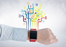 Mans wrist with smartwatch against digitally generated application icons. Close-up of mans wrist with smartwatch against digitally generated application icons Royalty Free Stock Image