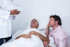 Mansammanträde bredvid patienter bäddar ned och lyssna till doktorn royaltyfri fotografi