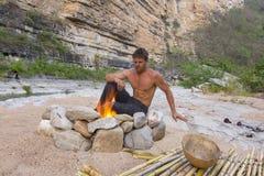 Mansammanträde på den primitiva campingplatsen med brand arkivfoto