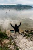 Mansammanträde på en stol på kusterna av en härlig sjö på en lugna vårafton med hans armar lyftte i beröm och glädje Royaltyfri Foto