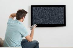 Mansammanträde på Sofa In Front Of Television Arkivfoton