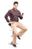 Mansammanträde på stol- och innehavmobiltelefonen royaltyfri fotografi
