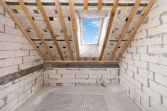 Mansard with environmentally friendly and energy efficient skylight window against blue sky. Room under construction with wooden beams, boards and windows stock photography