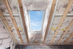 Mansard with environmentally friendly and energy efficient skylight window against blue sky. Room under construction with wooden b. Eams, boards and windows royalty free stock photos