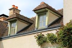 Mansardenfenster auf dem mit Ziegeln gedeckten Dach Stockfotos