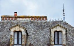 Mansardenfenster auf Schieferdach und orange Kaminen Rochefort-en-Terre, französische Bretagne stockfotografie