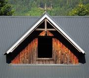 Mansardenfenster mit Holzverkleidung auf gemaltem grauem Metalldach Lizenzfreie Stockfotos