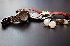 Manschett och klocka i träbakgrund arkivfoton