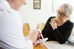 Manschettmodell To Senior Woman för doktor Explaining Shoulder Rotator arkivbilder