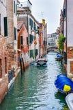 Mansegelbåt på kanalen för waterway/flodvatten mellan byggnader och folk som korsar den fot- bron i bakgrund i Venedig royaltyfri foto