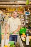 Manshopping i en supermarket arkivfoto