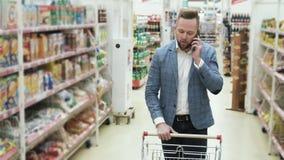 Manshopping på supermarket och samtal på telefonen, steadicamskott lager videofilmer