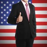 Manshowtumme upp med USA flaggan bak honom Royaltyfri Bild