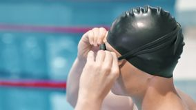 Mansimmare som sätter skyddsglasögon på framsidan för undervattens- sväva i simbassängsidosikt lager videofilmer