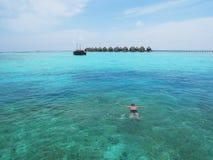 Mansimning i vatten för Maldiverna blåtthav nära en tropisk semesterort och traditionellt maldiviskt fartyg i bakgrunden royaltyfria foton