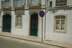 Mansion facade with cracked wall and NO WAITING road sign. On sunny day, in front of deserted causeway at Campo Maior. A little town with Roman, Moorish and royalty free stock image