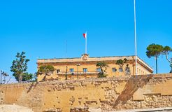 The mansion behind the fortress wall, Valletta, Malta. The mansion of former Vernon Club, nowadays - the Central Bank of Malta, behind the medieval wall of St Royalty Free Stock Photo