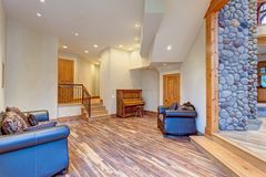 Mansion hallway interior with mixed wood floors. Mansion hallway interior accented with white ceiling over mixed wood floors. Fitted with leather sofas, a piano royalty free stock photo