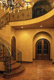 Mansion home interior front stairway entrance. Luxurious mansion home front entryway stairs with wrought iron railing Royalty Free Stock Image