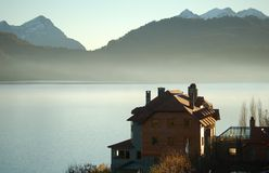 Mansion on lakeshore. Mansion on lake shore, mountains in the background, clear sky Royalty Free Stock Image