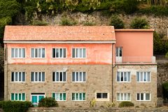 A mansion on a hill. A mansion on a slope with multiple windows, red tiled roof and stone walls stock image