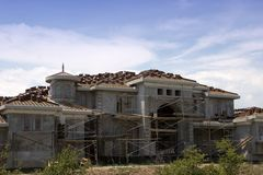 Mansion under Construction. A large, luxury mansion is under construction preparing for a stucco finish with red tile roof Royalty Free Stock Image
