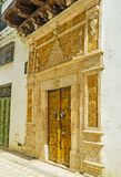 The entrance to historic mansion in Tunis medina. The mansions in Medina boasts unique, richly decorated gates with crved stone decors and wooden doors with Royalty Free Stock Photo