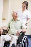 mansjuksköterska som skjuter rullstolen royaltyfri fotografi