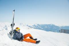 Manskidåkaren som vilar på berget, skidar semesterorten Royaltyfri Fotografi