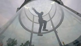 Manskydiveren flyger i vindtunnel Inomhus hoppa med fritt fall vindtunnel arkivfoto