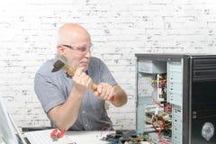 Manslag med en hammare på datoren royaltyfri fotografi