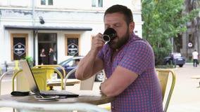 Manslut arbetar på bärbara datorn, drinkar kaffe och leenden för kamera i kafé, arkivfilmer