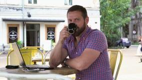 Manslut arbetar på bärbara datorn, drinkar kaffe och leenden för kamera i kafé, stock video