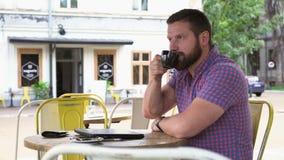 Manslut arbetar på bärbara datorn, drinkar kaffe och leenden för kamera i kafé lager videofilmer