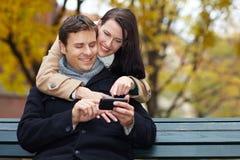 mansmartphone genom att använda kvinnan Royaltyfria Foton