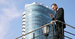 Mansms som smsar genom att använda app på den smarta telefonen i stad Stilig ung affärsman som använder att le för smartphone som arkivfilmer