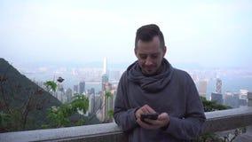 Mansms som smsar genom att använda app på den smarta telefonen i stad Stilig ung man som använder att le för smartphone som är ly stock video