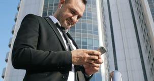 Mansms som smsar genom att använda app på den smarta telefonen i stadsaffärsområde Ung affärsman som använder att le för smartpho lager videofilmer