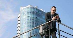 Mansms som smsar genom att använda app på den smarta telefonen i stadsaffärsområde Ung affärsman som använder att le för smartpho stock video