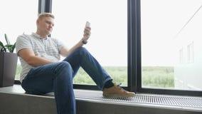 Mansms som smsar genom att använda app på den smarta telefonen på natten i stad Stilig ung affärsman som använder att le för smar lager videofilmer