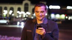 Mansms som smsar genom att använda app på den smarta telefonen på natten stock video