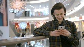 Mansms som smsar genom att använda app på den smarta telefonen på natten i stad Stilig ung affärsman som använder att le för smar stock video