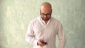 Mansms som smsar genom att använda app på den smarta telefonen Stilig ung affärsman som använder smartphonen som ler det lyckliga lager videofilmer