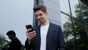 Mansms som smsar genom att använda app på smartphonen Affärsman som surfar internet med mobiltelefonen Stiligt grabbanseende på k lager videofilmer