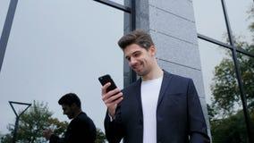Mansms som smsar genom att använda app på smartphonen Affärsman som surfar internet med mobiltelefonen Stiligt grabbanseende på k stock video