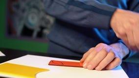 Mansnitt med glasskäraredetaljer av det framtida väggmålning- eller målat glassfönstret Hantverkarearbeten med kulört exponerings stock video
