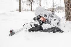 Mansoldat i vintern på en jakt med ett prickskyttgevär i vit vinterkamouflage som ligger i snön royaltyfri fotografi
