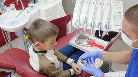 Manspecialisten in i medicinsk maskering visar tandprotesen i en konstgjord käke till ungen i tand- fåtölj arkivfilmer