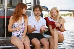Manspeeks med två härliga flickor på yachten royaltyfria bilder